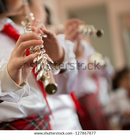 The pupils playing the flute.