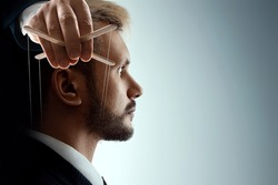 The puppeteer's male hand manipulates consciousness inside the human head. World conspiracy concept, world government, manipulation, control