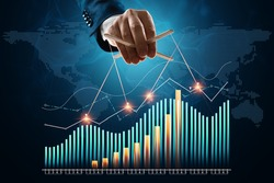 The puppeteer's male hand manipulates financial charts, business indicators. The concept of shadow government, world conspiracy, manipulation, control
