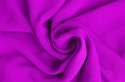 The purple fabric is rolled up in a spiral resembling a rose flower. Fabric and texture concept - close up on crumpled fabric background.