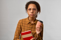 The puzzled student with a nervous indignant look on his face, holding a take-away coffee and a red textbook, isolated on a white background. A woman with dark skin looks intently into the camera.