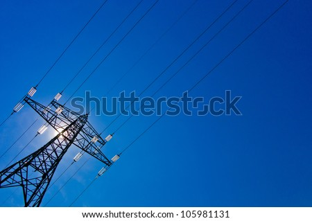 the pylons of a power line with sun and blue sky