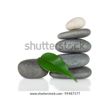 The pyramid of round stones with green leaf isolated on white background Foto stock ©
