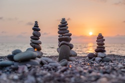 The pyramids of stones on the ocean coast - a symbol of tranquility and balance. Zen meditation concept. Beautiful sea sunset. Pebble beach. The background is natural. Relaxation therapy silence. Calm