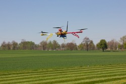 The quadrocopter flying over the green field