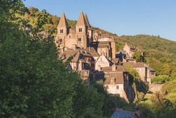 The quaint and charming medieval French village of Conques, Aveyron, and Abbey Church of Sainte-Foy, a popular summer tourist destination in the Occitanie region of France.