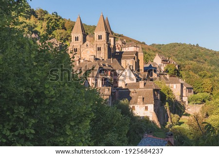 The quaint and charming medieval French village of Conques, Aveyron, and Abbey Church of Sainte-Foy, a popular summer tourist destination in the Occitanie region of France. Photo stock ©