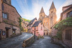 The quaint and charming medieval old town centre of the medieval French village Conques, Aveyron and Abbey Church of Sainte-Foy at sunset or sunrise in Occitanie, France.