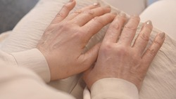 The quake hands of the old woman on her knees. Close-up. Top angle. Old shaking hands concept. Parkinson disease concept.