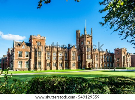 The Queen\'s University of Belfast with a grass lawn, tree branches and a hedge in sunset light