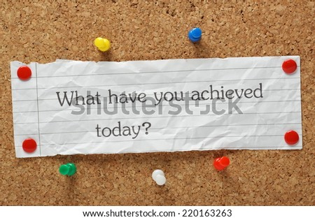The question What have you achieved today? typed on a piece of crumpled paper pinned to a cork notice board