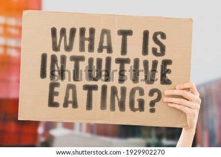 The question ' What is intuitive eating? ' on a banner in hand with blurred background. Food. Meal. Nutrition. Healthcare. Nutrient. Brain. Mind. Freedom. Free. Choice Stock foto ©