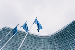 The queue of steeples with blue flags of the European Union against the background of the European Commission building in Brussels, Belgium. EU flag, symbol