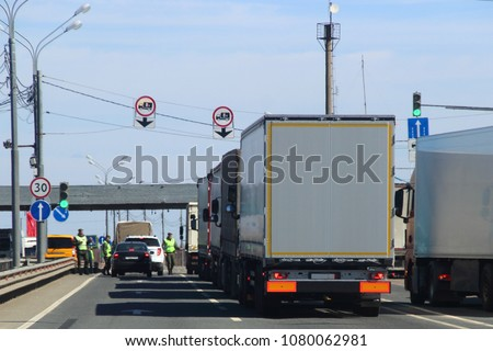 The queue of trucks with semi-trailers to the control point in the spring against the blue sky, inspectors in yellow jackets and camouflage check the documents of the driver of the car #1080062981