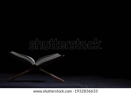 The Quran is placed on the plank in the mosque - open to prayers, the black background of Muslims around the world, placed on the wooden board, the Quran in the mosque - is open to prayer