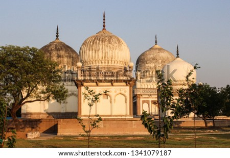 The Qutb Shahi Tombs are located in Hyderabad, India.  The tombs form a large cluster and stand on a raised platform. The tombs are domed structures built on a square base surrounded by pointed arches #1341079187