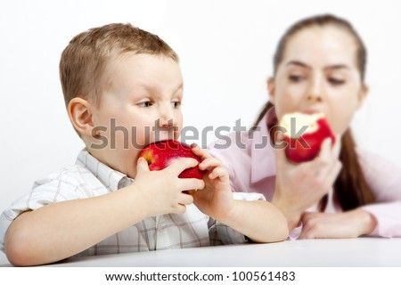 The race: Who  the first  will eat apple? In the foreground a boy eats the apple. In the background a woman. They are focused and very hungry.