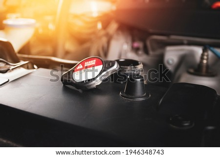 The radiator cap 1.1 bar is open and placed on radiator of the car engine with a sunlight