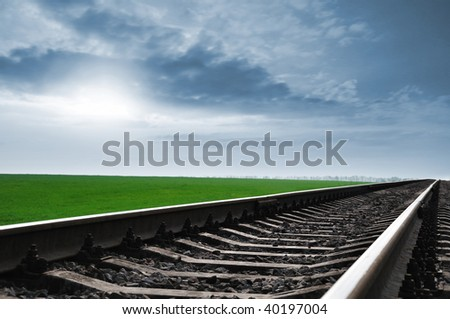 The railway leaving in a distance under the blue sky