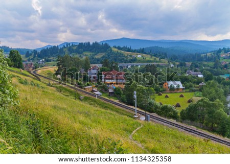 The railway passes between the mountain slopes along the shrouded greenery of the village against the background of mist-covered mountain peaks under a cloudy sky. place of rest and tourism #1134325358