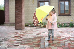 The rain has just ended. Little girl standing under a children's umbrella.  The girl is wearing rubber boots and a raincoat.