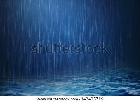 the rain water drop falling to the dark surface water in rainy season