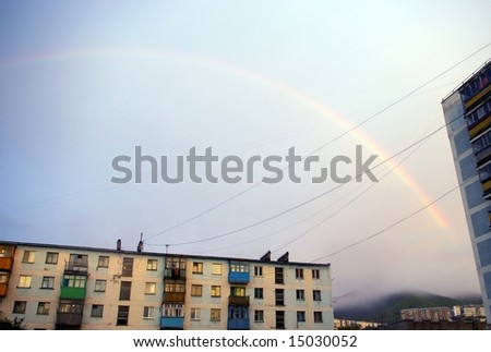 The Rainbow on city at evening , before sundown.The Rainbow and house, which is painted in crimson light calling at sun, twilight