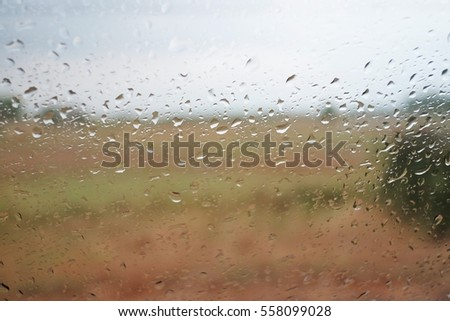 The rains drop on the windows during drive a car on the rood in rainy season at vintage background in  the morning.