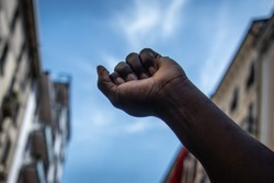 The raised fist. A black man raises his fist to the sky during a migrants protest against racial discrimation. Black power, revolution. Black Lives Matter