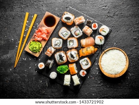 The range of different types of sushi, rolls and Maki with sauces and chopsticks. On black rustic background