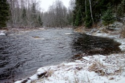 The rapid flow of dark water in the middle of the river emphasizes the calmness of white snow on the banks of the river