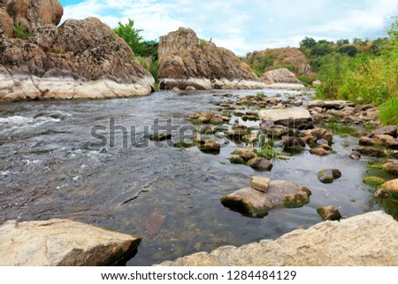 The rapid flow of the river, rocky shores, rapids, bright green vegetation and a cloudy blue sky in summer. Southern Bug River. Ukraine.