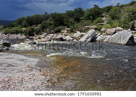 The rapids. View of the river flowing across the stone valley in the mountain forest. Th shallows, foamy water and rocky shore and bed.   Photo stock ©