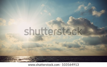 The rays of the sun breaking through clouds over the sea