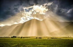 The rays of the sun from behind the clouds illuminate the valley. Sunrays from sky clouds. Cloudy sky sunrays. Beautiful sunrays from cloudy sky
