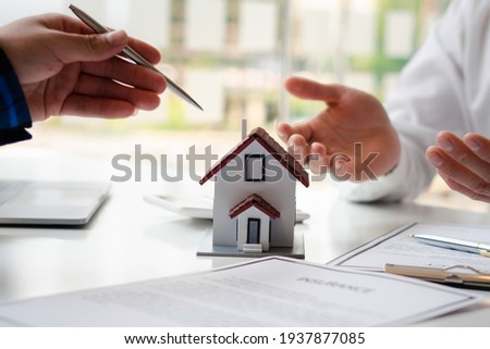 The real estate agent is explaining the house style to the clients who come to contact to see the house design and the purchase agreement. Within a modern office