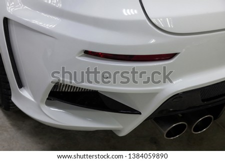 The rear bumper of a tuned car is white with a double exhaust nozzle, a diffuser and a red reflector in a vehicle tuning workshop. Auto service industry #1384059890