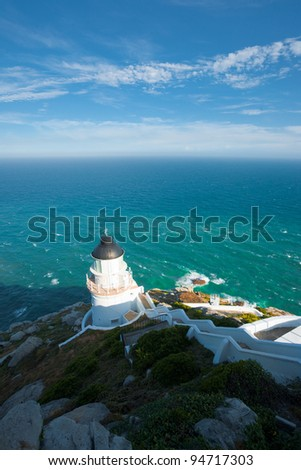 The rear of Dongyong lighthouse and green ocean seen from behind high atop the steep hill on Dongyin island on the Matsu archipelago in Taiwan. Vertical copy space