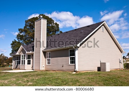 The rear view of a home with slab patio and background of blue sky with clouds.