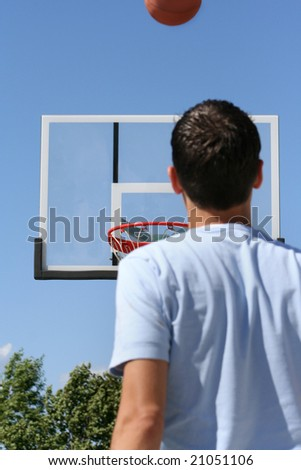 The rear view of a young boy facing a hoop as a basketball ascends toward it. Horizontally framed shot.