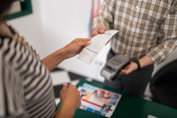 The receipt in hands. Close-up photo of seller handing the receipt to the customer during purchasing process.