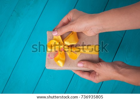 The receipt of gifts. Female hands holding a gift. The girl unpacks the gift. The woman gives you a gift. Yellow bow on the gift.