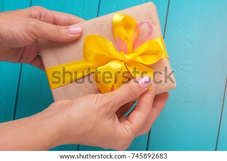 The receipt of gifts. Female hands holding a gift. The girl unpacks the gift. The woman gives you a gift. Yellow bow on the gift. The background color of a sea wave. Rotated view with flash