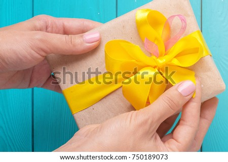 The receipt of gifts. Female hands holding a gift. The girl unpacks the gift. The woman gives you a gift. Lighting a bright flash. A ray of light on a blue background