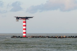 The red and white striped lighthouse with heliplatform at the entrance of the Port of Rotterdam in the Netherlands. The lighthouse is situated at the end of a pier with concrete wave breakers.