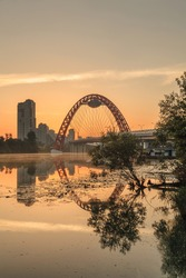The Red Arch of the Picturesque bridge in Moscow across the river early in the morning at dawn. Urban summer landscape. Contrast bright light. Travel to the capital of Russia. High-rise buildings.