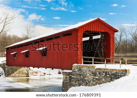 The red Cataract Falls Covered Bridge crosses Indiana's Mill Creek with a snowy landscape and deep blue, cloud-draped sky.