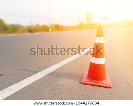 The red cone is placed to prevent danger from road operations. #1344276884