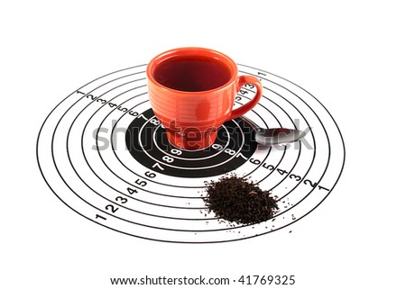 The red cup with tea is in the centre of a target for accuracy training, nearby there is a teaspoon and tea leaves are scattered. The creative with idea tea - hit in the purpose, tea is your choice.