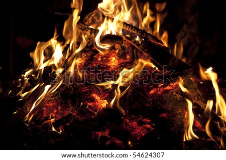 The red embers and flames in the fire at night background